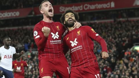 Liverpool's Mohamed Salah, right, celebrates with his teammate Jordan Henderson after scoring his side's second goal during the English Premier League soccer match between Liverpool and Tottenham Hotspur at Anfield stadium in Liverpool, England, Sunday, Oct. 27, 2019. (AP Photo/Jon Super)