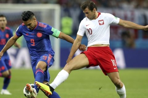 Colombia's Radamel Falcao, left, and Poland's Grzegorz Krychowiak, right, challenge for the ball during the group H match between Poland and Colombia at the 2018 soccer World Cup at the Kazan Arena in Kazan, Russia, Sunday, June 24, 2018. (AP Photo/Thanassis Stavrakis)