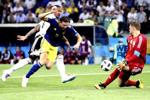 Germany goalkeeper Manuel Neuer, right, makes a save in front of Sweden's Marcus Berg, center, during the group F match between Germany and Sweden at the 2018 soccer World Cup in the Fisht Stadium in Sochi, Russia, Saturday, June 23, 2018. (AP Photo/Thanassis Stavrakis)