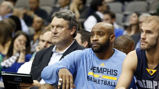 Memphis Grizzlies' Vince Carter, left with his right ankle iced, sits next to Nick Calathes, right, on the bench late in the second half of a preseason NBA basketball game against the Dallas Mavericks, Monday, Oct. 20, 2014, in Dallas. The Mavericks won 108-103. (AP Photo/Tony Gutierrez)