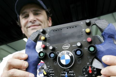 Two-time CART champion Alex Zanardi, who lost both of his legs in a horrific crash over five years ago, shows the modified steering wheel of his BMW-Sauber C24-B during a test at the Cheste racetrack near Valencia, Spain, Sunday Nov. 26, 2006. Zanardi is the first double amputee to test drive a Formula One car. (AP Photo/Fernando Bustamante)