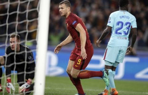 Roma's Edin Dzeko, center, celebrates after scoring his side's opening goal during the Champions League quarterfinal second leg soccer match between Roma and FC Barcelona at Rome's Olympic Stadium, Tuesday, April 10, 2018. (AP Photo/Andrew Medichini)