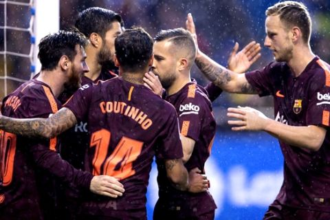 Barcelona's Lionel Messi, left, is congratulated by teammates after scoring a goal during a Spanish La Liga soccer match between Deportivo and Barcelona at the Riazor stadium in A Coruna, Spain, Sunday, April 29, 2018. (AP Photo/Lalo R. Villar)