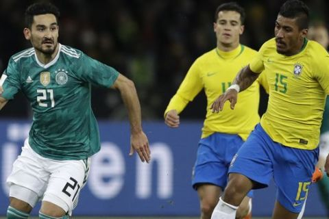 Germany's Ilkay Gundogan, left, is challenged by Brazil's Paulinho during the international friendly soccer match between Germany and Brazil in Berlin, Germany, Tuesday, March 27, 2018. (AP Photo/Michael Sohn)