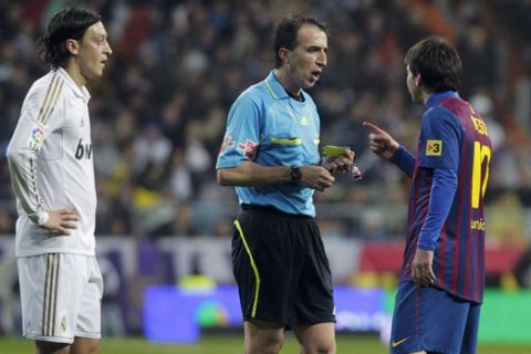 In this photo taken Saturday, Dec. 10, 2011, Real Madrid's Mesut Ozil from Germany, left, listens to FC Barcelona's Lionel Messi from Argentina, right, talking with referee Fernandez Borbalan, centre, during their Spanish La Liga soccer match at the Santiago Bernabeu stadium in Madrid, Spain. (AP Photo/Andres Kudacki)