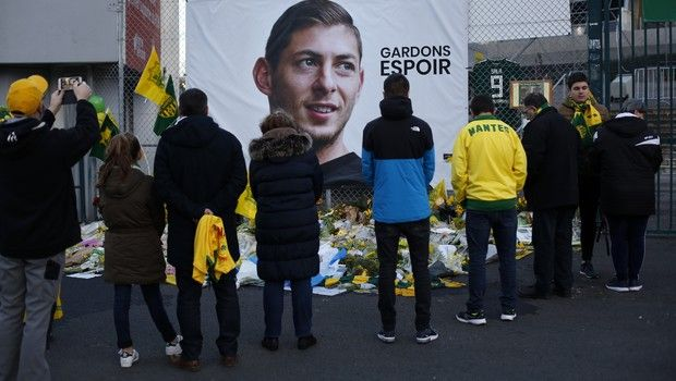 Nantes soccer team supporters stand in front of a poster of Argentinian player Emiliano Sala outside La Beaujoire stadium before the French soccer League One match Nantes against Saint Etienne, in Nantes, western France, Wednesday, Jan.30, 2019. Sala disappeared over the English Channel on Jan. 21, 2019 as it flew from France to Wales. Sala had just been signed by Premier League club Cardiff. (AP Photo/Thibault Camus)
