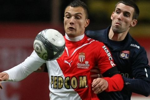 Monaco's Yohan Mollo of France, left, vies for the ball with Lyon's Anthony Reveillere of France, right, during their French League One soccer match, in Monaco stadium, Sunday, Dec. 20, 2009. (AP Photo/Lionel Cironneau)