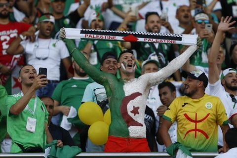 Algerian fans cheer before the African Cup of Nations group C soccer match between Algeria and Senegal at 30 June Stadium in Cairo, Egypt, Thursday, June 27, 2019. (AP Photo/Ariel Schalit)