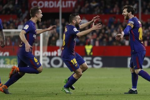 Barcelona's Messi, right, celebrates with teammates after scoring against Sevilla during La Liga soccer match between Barcelona and Sevilla at the Sanchez Pizjuan stadium, in Seville, Spain on Saturday, March 31, 2018. (AP Photo/Miguel Morenatti)