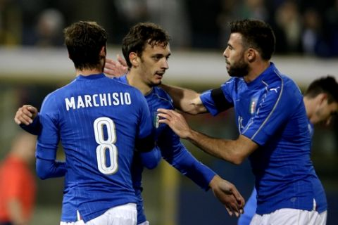 Italys Manolo Gabbiadini, center,  celebrates with his teammates Claudio Marchisio, left, and Andrea Barzagli  after scoring during a friendly soccer match between Italy and Romania at the Renato Dall'Ara stadium in Bologna, Italy, Tuesday, Nov. 17, 2015. (AP Photo/Luca Bruno)