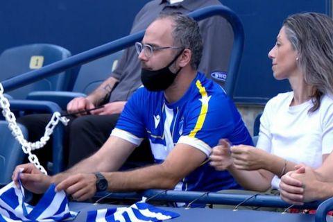 Έλληνας οπαδός παρακολουθεί αγώνα του Στέφανου Τσιτσιπά φορώντας φανέλα Αστέρα Τρίπολης και ΑΠΟΕΛ