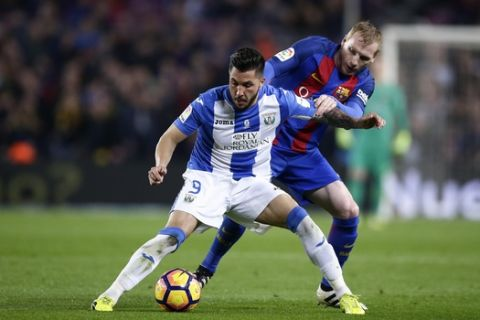 FC Barcelona's Jeremy Mathieu, right, duels for the ball against Leganes' Miguel Angel Guerrero during the Spanish La Liga soccer match between FC Barcelona and Leganes at the Camp Nou stadium in Barcelona, Spain, Sunday, Feb. 19, 2017. (AP Photo/Manu Fernandez)