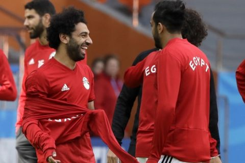 Egypt's Mohamed Salah, left, jokes with teammates during Egypt's official training on the eve of the group A match between Egypt and Uruguay at the 2018 soccer World Cup in the Yekaterinburg Arena, Yekaterinburg, Russia, Thursday, June 14, 2018. (AP Photo/Mark Baker)