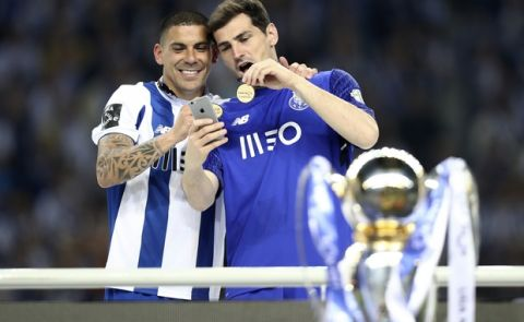 Porto goalkeeper Iker Casillas and teammate Maxi Pereira, left, take a selfie with their medals at the end of the Portuguese league soccer match between FC Porto and Feirense at the Dragao stadium in Porto, Portugal, Sunday, May 6, 2018. Porto clinched the league title Saturday night, two rounds before the end, when Benfica and Sporting CP tied 0-0 in their Lisbon derby. (AP Photo/Luis Vieira)