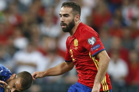 Italy's Leonardo Spinazzola falls next to Spain's Sergio Busquets and Dani Carvajal during the World Cup Group G qualifying soccer match between Spain and Italy at the Santiago Bernabeu stadium in Madrid, Spain, Saturday, Sept. 2, 2017. (AP Photo/Francisco Seco)