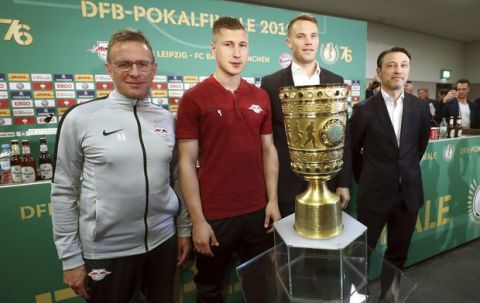 Leipzig head coach Ralf Rangnick, his captain Willi Orban, Munich's captain Manuel Neuer and head coach Niko Kovac, from left, stand behind the German soccer cup trophy in Berlin, Germany, Friday, May 24, 2019. Fifty-four major titles compared to none, 119 years of existence against 10, some 290,000 club members versus 17  the contrast between Bayern Munich and Leipzig could hardly be greater. The clubs meet in the German Cup final on Saturday, when Leipzig will bid for its first ever title and Bayern will hope to bring a happy end to a testing season with another domestic double. (Christian Charisius/dpa via AP)