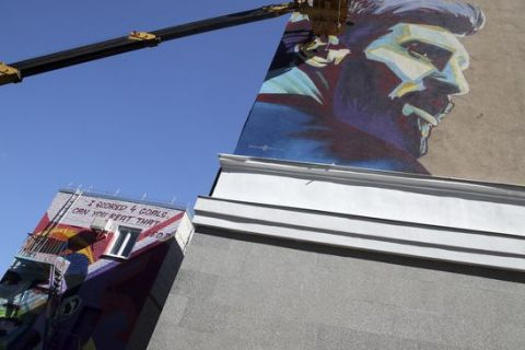 Russian graffiti artists of the SuperNovaNet team make a mural of Argentina's Lionel Messi as their older project with Portugal's Cristiano Ronaldo portrait is seen next to the hotel of Argentina team during the 2018 soccer World Cup in Kazan, Russia, Friday, June 29, 2018. (AP Photo/Thanassis Stavrakis)