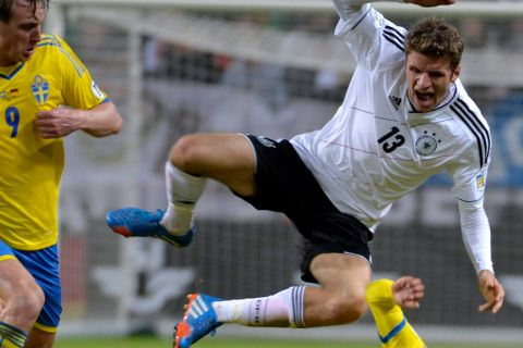 Germany's Thomas Muller, top, jumps over Sweden's Martin Olsson as Sweden's Kim Kallstrom, left, looks on during the 2014 World Cup group C qualifying soccer match between Sweden and Germany at Friends Arena in Stockholm, Sweden, on Tuesday Oct. 15, 2013. (AP Photo/TT, Anders Wiklund)  SWEDEN OUT