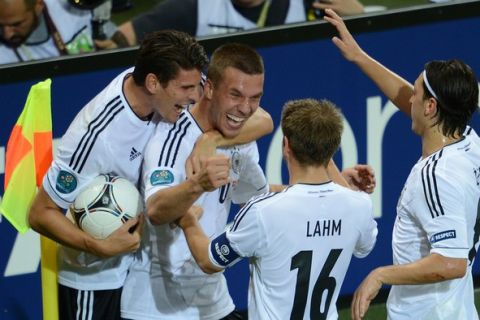 German forward Lukas Podolski  (2ndL) is congratulated by teammates after scoring a goal during the Euro 2012 football championships match Denmark vs. Germany, on June 17, 2012 at the Arena Lviv in Lviv. AFP PHOTO / PATRIK STOLLARZ        (Photo credit should read PATRIK STOLLARZ/AFP/GettyImages)