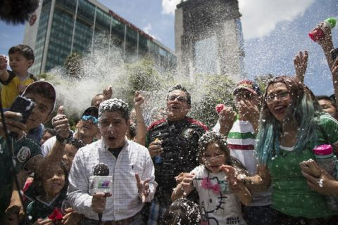A reporter and fans are covered in foam during the celebration of Mexico's 2018 World Cup win over Germany at the Angel of Independence in Mexico City, Sunday, June 17, 2018. Mexico won it's first match against Germany 1-0. (AP Photo/Anthony Vazquez)