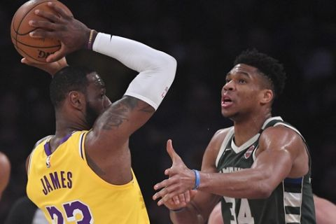 Los Angeles Lakers forward LeBron James, left, tries to pass as Milwaukee Bucks forward Giannis Antetokounmpo guards him during the first half of an NBA basketball game Friday, March 6, 2020, in Los Angeles. (AP Photo/Mark J. Terrill)