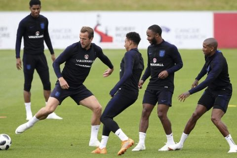 England's Harry Kane, left, controls the ball during a training session at St George's Park, in Burton, England,  Monday May 28, 2018. England will play Nigeria in an international friendly match on Saturday. (Nick Potts/PA  via AP)