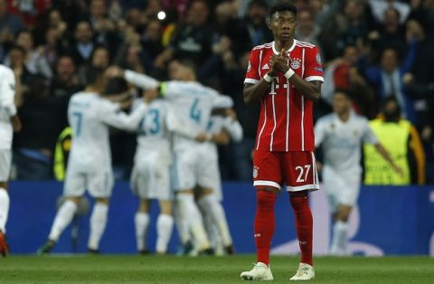 Bayern's David Alaba reacts when Madrid players celebrate after scoring their second goal during the Champions League semifinal second leg soccer match between Real Madrid and FC Bayern Munich at the Santiago Bernabeu stadium in Madrid, Spain, Tuesday, May 1, 2018. (AP Photo/Paul White)