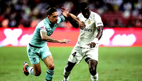 Paris Saint-Germain's Stanley Nsoki, right, competes for the ball with Arsenal's Hector Bellerin during the International Champions Cup match between Arsenal and Paris Saint-Germain in Singapore, Saturday, July 28, 2018. (AP Photo/Yong Teck Lim)