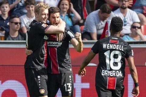 Leverkusen's Lucas Alario, center, celebrates after scoring during the German Bundesliga soccer match between Bayer Leverkusen and 1.FC Nuremberg in Leverkusen, Germany, Saturday, April 20, 2019. (Guido Kirchner/dpa via AP)
