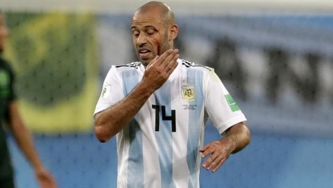 Argentina's Javier Mascherano touches his face after an injuring during the group D match between Argentina and Nigeria, at the 2018 soccer World Cup in the St. Petersburg Stadium in St. Petersburg, Russia, Tuesday, June 26, 2018. (AP Photo/Petr David Josek)