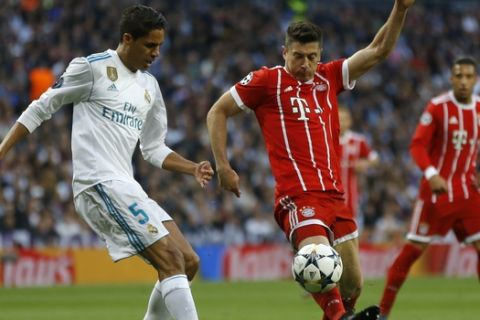 Real Madrid's Raphael Varene, left, and Bayern's Robert Lewandowski challenge for the ball during the Champions League semifinal second leg soccer match between Real Madrid and FC Bayern Munich at the Santiago Bernabeu stadium in Madrid, Spain, Tuesday, May 1, 2018. (AP Photo/Francisco Seco)