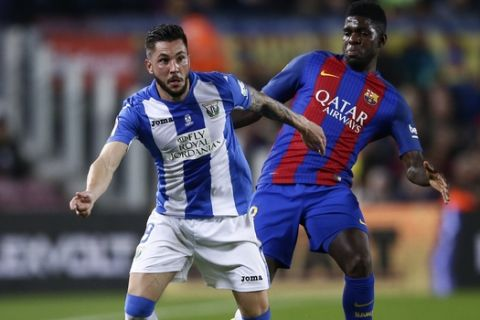 FC Barcelona's Samuel Umtiti, right, duels for the ball against Leganes' Miguel Angel Guerrero during the Spanish La Liga soccer match between FC Barcelona and Leganes at the Camp Nou stadium in Barcelona, Spain, Sunday, Feb. 19, 2017. (AP Photo/Manu Fernandez)