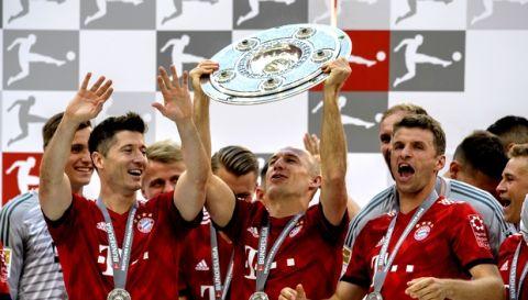 Bayern's Robert Lewandowski, Arjen Robben and Thomas Mueller, from left, celebrate with the Bundesliga trophy after the Bundesliga soccer match between Bayern Munich and VfB Stuttgart in Munich, southern Germany, Saturday, May 12, 2018. (Matthias Balk/dpa via AP)