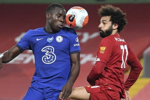 Chelsea's Kurt Zouma, left, and Liverpool's Mohamed Salah battle for the ball during the English Premier League soccer match between Liverpool and Chelsea at Anfield stadium in Liverpool, England, Wednesday, July 22, 2020. (Laurence Griffiths, Pool via AP)