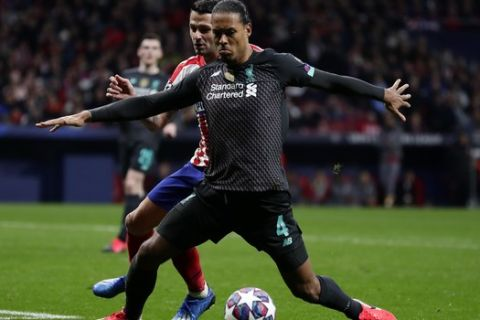 Liverpool's Virgil van Dijk, foreground, controls the ball past Atletico Madrid's Sime Vrsaljko during a 1st leg, round of 16, of the Champions League soccer match between Atletico Madrid and Liverpool at the Wanda Metropolitano stadium in Madrid, Tuesday, Feb. 18, 2020. (AP Photo/Manu Fernandez)