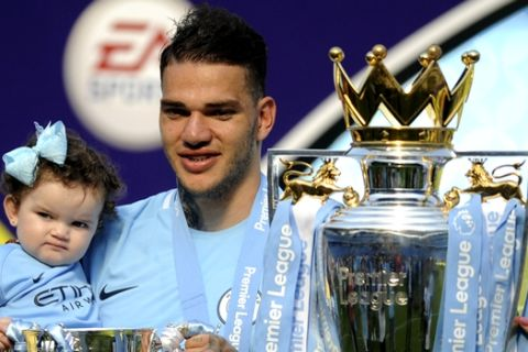 Manchester City's goalkeeper Ederson Moraes poses with his daughter Yasmin during celebrations for winning the English Premier League after the soccer match between Manchester City and Huddersfield Town at Etihad stadium in Manchester, England, Sunday, May 6, 2018. (AP Photo/Rui Vieira)