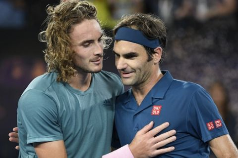 Greece's Stefanos Tsitsipas, left, is congratulated by Switzerland's Roger Federer after winning their fourth round match at the Australian Open tennis championships in Melbourne, Australia, Sunday, Jan. 20, 2019. (AP Photo/Andy Brownbill)