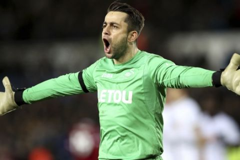 Swansea City goalkeeper Lukasz Fabianski celebrates at the end of the English Premier League soccer match between Swansea City and Liverpool, at the Liberty Stadium, in Swansea, Wales, Monday, Jan. 22, 2018. (Nick Potts/PA via AP)
