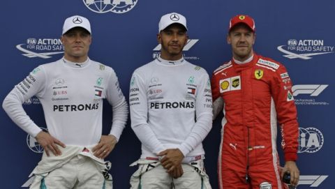Mercedes driver Lewis Hamilton of Britain, centre, who clocked the fastest time to claim pole position, stands next to 2nd placed Mercedes driver Valtteri Bottas of Finland, left and 3rd placed Ferrari driver Sebastian Vettel of Germany after qualifying practice at the Paul Ricard racetrack, in Le Castellet, southern France, Saturday, June 23, 2018. The Formula one race will be held on Sunday. (AP Photo/Claude Paris)