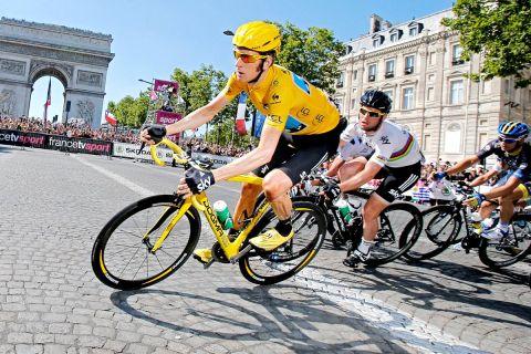"""Η κίτρινη φανέλα (Μπράντλεϊ Γουίγκινς) οδηγεί τον παγκόσμιο πρωταθλητή (Μαρκ Κάβεντις) στο Παρίσι με φόντο την Αψίδα του Θριάμβου. Λίγα λεπτά αργότερα, ο """"Καβ"""" θα πετύχει την τέταρτη συνεχόμενη νίκη του στα Ηλύσια Πεδία (22/7/2012)."""