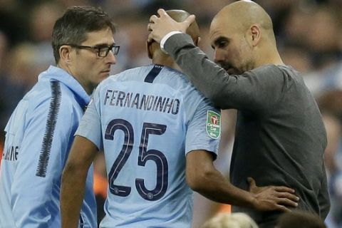 Manchester City manager Josep Guardiola, right, speaks with Manchester City's Fernandinho, center, during the English League Cup final soccer match between Chelsea and Manchester City at Wembley stadium in London, England, Sunday, Feb. 24, 2019. (AP Photo/Tim Ireland)