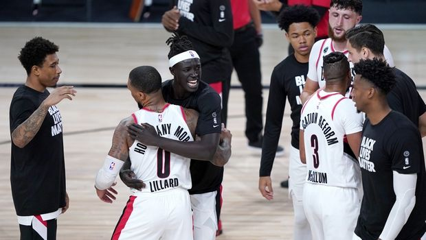 Portland Trail Blazers' Damian Lillard (0) is hugged by teammate Wenyen Gabriel after defeating the Brooklyn Nets during an NBA basketball game Thursday, Aug. 13, 2020, in Lake Buena Vista, Fla. The Trail Blazers won 134-133. (AP Photo/Ashley Landis, Pool)