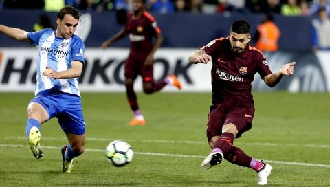 Malaga's Ignasi Miquel fights for the ball against Barcelona's Luis Suarez, right, during a Spanish La Liga soccer match between Malaga and Barcelona in Malaga, Spain, Saturday, March 10, 2018. (AP Photo/M.Pozo)