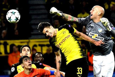 Dortmund's Julian Weigl, left center, jumps for the ball with APOEL's goalkeeper Nauzet Perez during the Champions League group H soccer match between Borussia Dortmund and APOEL Nicosia in Dortmund, Germany, Wednesday, Nov. 1, 2017. (AP Photo/Martin Meissner)