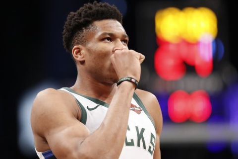 Milwaukee Bucks forward Giannis Antetokounmpo (34) blows on his hand before the start of the first quarter of an NBA basketball game Brooklyn Nets, Monday, Feb. 4, 2019, in New York. (AP Photo/Kathy Willens)