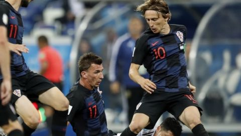 Argentina's Lucas Biglia, on the ground, fights for the ball with Croatia's Mario Mandzukic, left, and Luka Modric during the group D match between Argentina and Croatia at the 2018 soccer World Cup in Nizhny Novgorod Stadium in Novgorod, Russia, Thursday, June 21, 2018. (AP Photo/Pavel Golovkin)