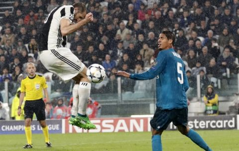 Juventus' Giorgio Chiellini, left, duels for the ball with Real Madrid's Raphael Varane during the Champions League first leg quarter final soccer match between Juventus and Real Madrid, at Juventus Stadium in Turin, Italy, Tuesday, April 3, 2018. (AP Photo/Antonio Calanni)