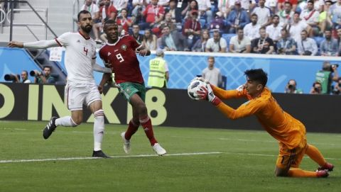 Iran goalkeeper Ali Beiranvand, right, stops the ball as Morocco's Ayoub El Kaabi, center, and Iran's Roozbeh Cheshmi, left, follow the ball during the group B match between Morocco and Iran at the 2018 soccer World Cup in the St. Petersburg Stadium in St. Petersburg, Russia, Friday, June 15, 2018. (AP Photo/Themba Hadebe)