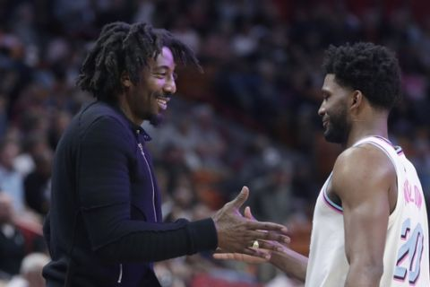Former NBA basketball player Amar'e Stoudemire, left, greets Miami Heat's Justise Winslow (20) during the first half of an NBA basketball game between the Miami Heat and Phoenix Suns, Monday, March 5, 2018, in Miami. (AP Photo/Lynne Sladky)