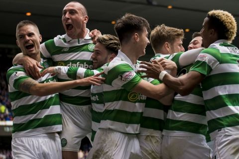 Celtic's Callum McGregor celebrates with teammates after scoring his sides' third goal of the game during their Scottish Premiership soccer match against Rangers at the Ibrox Stadium, Glasgow, Scotland, Saturday, April 29, 2017. Celtic dished out one last humiliation to hapless Rangers as their 5-1 win at Ibrox took them to within five games of an unbeaten domestic campaign. The Parkhead faithful lapped up every moment of this season's sixth and final Old Firm duel as Brendan Rodgers' undefeated troops outclassed a feeble Rangers line-up from start to finish. (Craig Watson/PA via AP)